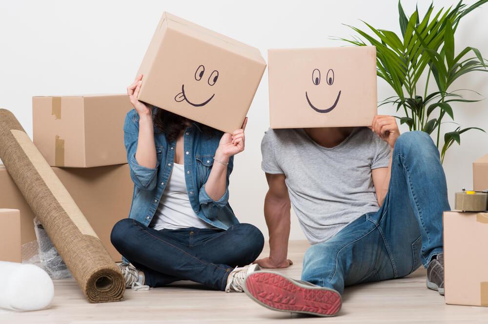 dos personas con cajas de carton en la cabeza en una mudanza